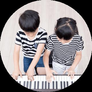 男の子と女の子が一緒にピアノを弾いている写真